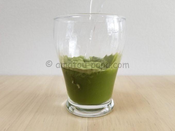 青汁の粉末が入ったコップに水を注ぎ溶けていく