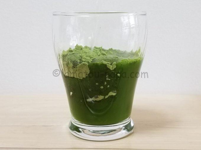 青汁粉末が入ったコップに水を注ぎ、青汁粉末が溶けていく
