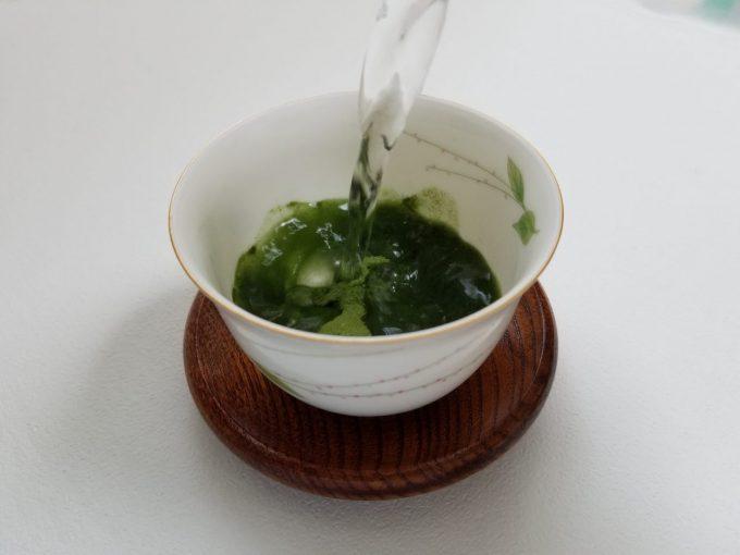 青汁の粉末を入れた湯呑みにぬるま湯を注いでいる