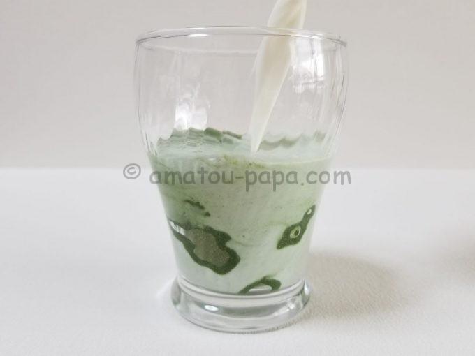 青汁の粉末が入ったコップに牛乳を注ぎ、青汁粉末が混ざっていく
