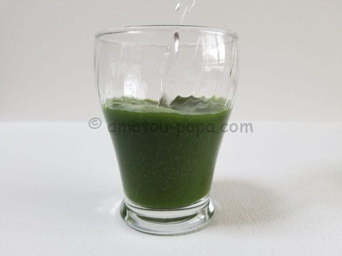 青汁の粉末が入ったコップに水を注ぎ、粉末が混ざっていく
