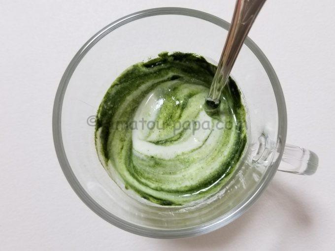 スプーンでかき混ぜている途中の、マーブル状に混ざった青汁ヨーグルトを真上から見る