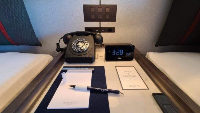 メズム東京、オートグラフ コレクションのchapter 1(ダブル、ガーデンビュー、バルコニー)のベッドサイドにあるペンと電話と時計